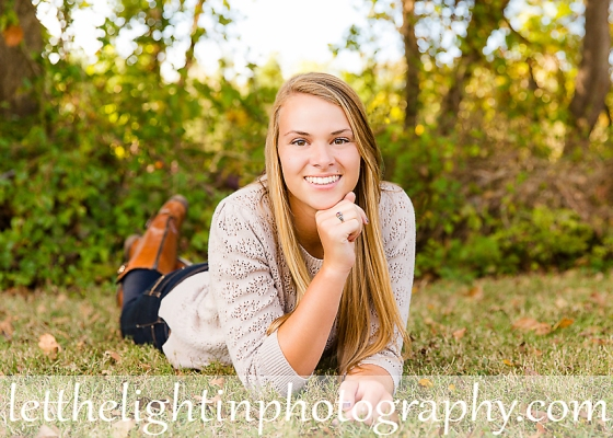Girl who is a Senior in High School Posing for her Senior Pictures in the grass