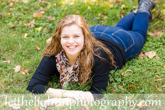 Senior girl laying in the grass posing for her Senior Pictures
