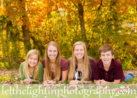 4 siblings laying on the ground posing for a photo in the fall in Haymarket VA