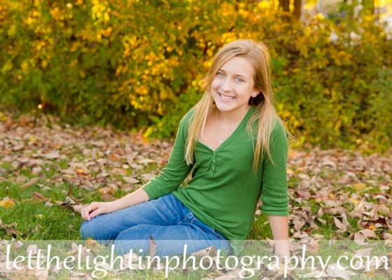 Teen girl sitting in the grass posing for a photo by local photographer in Haymarket VA