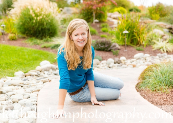 Girl sitting on a sidewalk posing for Senior Portraits in Bristow VA