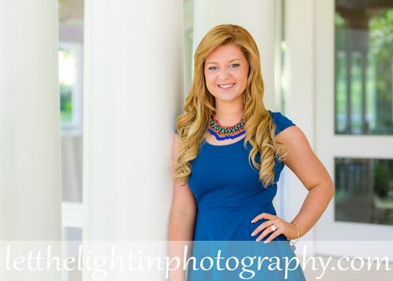 girl in blue dress leaning against white column for her Senior Portriats