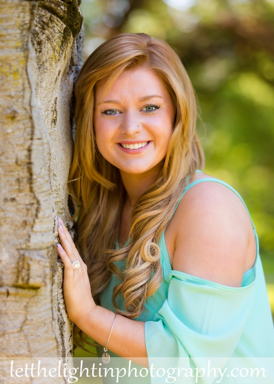 Girl poses for her Senior Portraits beside a tree.