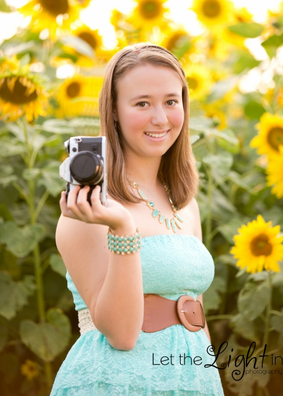 Senior girl holding camera, sunflowers in background by local portrait photographer in Haymarket VA Wendy Atkinson