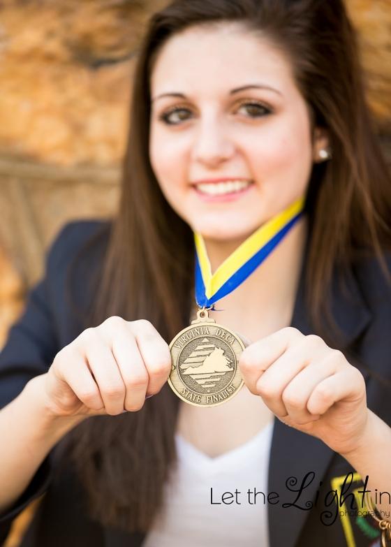 girl showing her DECA medal during her Senior Portrait Session