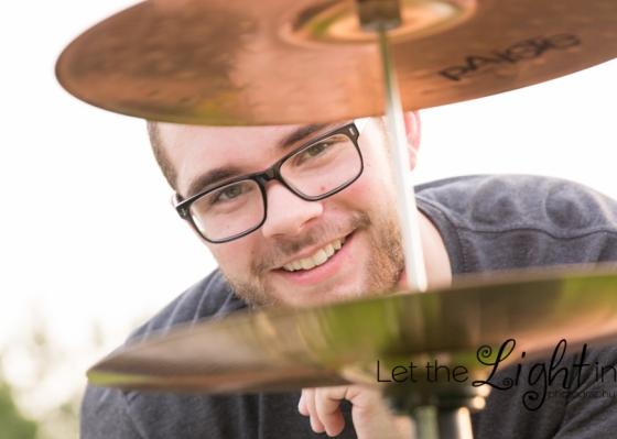 Senior drummer looking through cymbals
