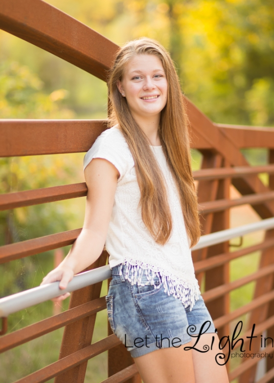 Senior girl leaning against iron bridge