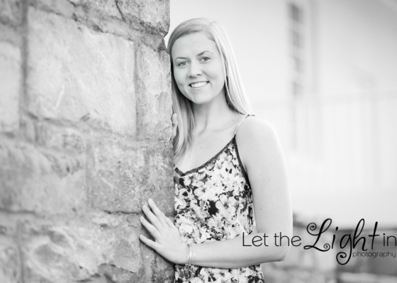 black and white photo of senior girl leaning against a stone wall in Haymarket VA for her Senior Pictures
